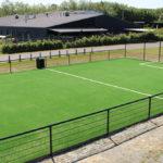 Udendørs boldbane med kunstgræs og sort hegn